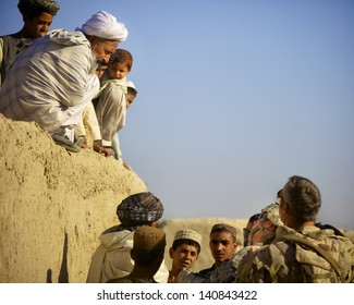 KANDAHAR, AFGHANISTAN - OCTOBER 8: An Afghan village elder talks to ISAF forces from atop his home on October 8, 2010 in Kandahar Province Afghanistan.