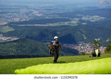 KANDEL, WALDKIRCH, GERMANY - JUNE 22, 2018: Paraglider preparing his parachute on the grid, waiting for the right wind before taking off from the Kandel mountain, Waldkirch, Gemany
