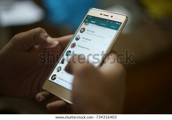 "KANDIVALI, MUMBAI, MAHARASHTRA, INDIA - OCTOBER 10, 2017- A guy is using ""WhatsApp"" application on his cell phone at home in Mumbai, India."