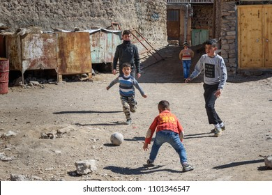 Kandovan, East Azerbaijan province, Iran - March 16, 2018: TYoung Iranian boys play football on the street in rock village Kandovan