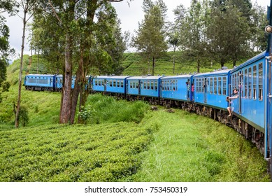 KANDY ELLA, SRI LANKA. September 17, 2017. People hanging out of the famous blue train driving through tea plantations. Train route between Kandy and Ella is extremely beautiful. Train in Sri Lanka.