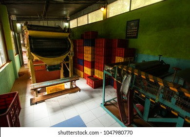 Kandy, Sri Lanka - April 12th, 2017: Empty room with tea dryer machine at Kadugannawa Tea Factory, plastic boxes with processed tea in back. Some of finest tea in the world is produced in Sri Lanka