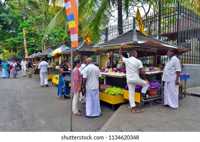 Kandy, Sri Lanka - April 6, 2018: Vendors of floral religious offerings on Temple St, near the  entrance gate of the Temple of the Sacred Tooth.