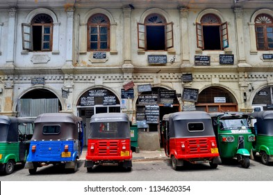 Kandy, Sri Lanka - April 6, 2018: Colorful tuk-tuks parked in front of an historical building of Deva Veediya.