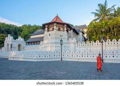 Kandy, Sri Lanka - April 6th, 2019. A Buddhist munk walks past the Temple of the Tooth, Kandy, Sri Lanka.