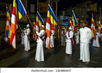 KANDY, SRI LANKA - AUGUST 02, 2017 : Buddhist Flag Bearers parade along a street in Kandy during the Esala Perahera (great procession).