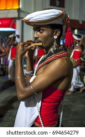 KANDY, SRI LANKA - AUGUST 04, 2017 : A Flute Player performs along the streets of Kandy in Sri Lanka during the Esala Perahera (great procession). The perahera honours the sacred tooth relic of Buddha