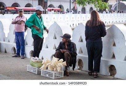 KANDY/ SRI LANKA, AUGUST 04-2019: Unspecific people around the lake. in everyday life. Someone who sell somethig for his life.