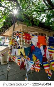 KANDY, SRI LANKA - AUGUST 09, 2013 : A display of Sri Lankan flags and colourful cloth attached to a pole under a tree within the Temple of the Sacred Tooth Relic complex in Kandy in Sri Lanka.