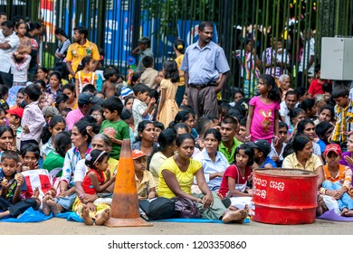KANDY, SRI LANKA - AUGUST 11, 2013 : A huge crowd of people sit along a street in Kandy prior to the commencement of the Buddhist Esala Perahera (great procession).