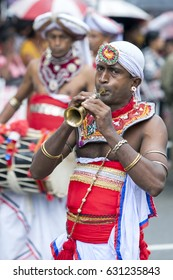 KANDY, SRI LANKA - AUGUST 11, 2014 : A Trumpet Player performs along the streets of Kandy during Day Perahera on the final day of the Esala Perahera which is held to honour the sacred tooth relic.