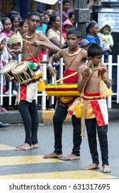 KANDY, SRI LANKA - AUGUST 11, 2014 : Young musicians including drummers and a cymbal player perform along the streets of Kandy during the Day Perahera on the last day of the Esala Perahera.