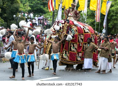 KANDY, SRI LANKA - AUGUST 11, 2014 : Chamara Dancers perform ahead of a ceremonial elephant carrying a temple priest along the streets of Kandy during the Day Perahera.