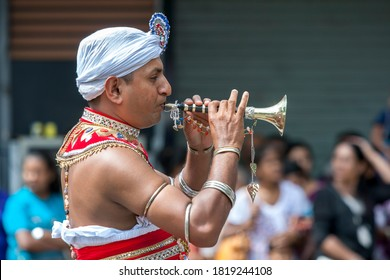 KANDY, SRI LANKA - AUGUST 15, 2019 : A  Trumpet Blower performs along a street in Kandy during the Day Perahera, the final parade of the Buddhist Esala Perahera festival.