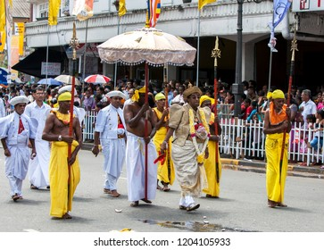 KANDY, SRI LANKA - AUGUST 30, 2015 : A Buddhist Temple Priest accompanied by ceremonial guards marches along a street in Kandy during the Day Perahera which is the final event of the Esala Perahera.