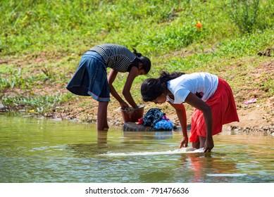 KANDY, SRI LANKA - CIRCA DECEMBER 2013: Unidentified Sri Lankan girls wash cloth