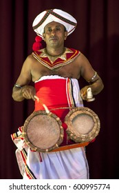 KANDY, SRI LANKA - JULY 28, 2012 : A Thammattam Player performs at the Esala Perahera Theatre Show. The drum is tied around the performers waist to allow free movement of the hands and feet.