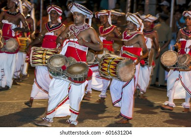 KANDY, SRI LANKA - JULY 30, 2012 : A Thammattam Player (centre) and Davul Players perform through the streets during the Esala Perahera. The perahera is held to honour the sacred tooth relic of Buddha