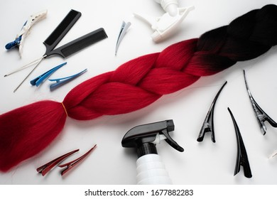 Kanekalon two- color-artificial hair Ombre red and black for braiding braids, lying on a white background next to accessories