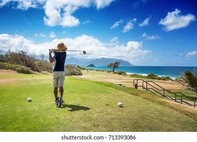KANEOHE, HAWAII - AUG 27: Man with straw hat and shades teeing off at Klipper Marine Golf Course in Kaneohe, Hawaii on August 27, 2017. Its famous as President Obama's favorite golf course in Hawaii.