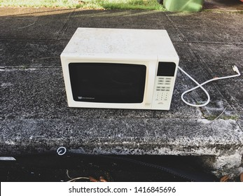 Kaneohe, Hawaii / USA - May 5, 2019. Old white microwave sits on a street curb in a residential neighborhood to be picked up by a garbage truck. Landfill, waste, cheap products, planned obsolescence.