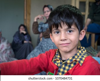 Kang, Iran - July 30, 2016 : portrait of an iranian child with his family in background