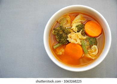 Kang Som. Spicy and sour soup with mix vegetables in white bowl. Soup from fish and herb mix of carrot, broccoli, long bean and chinese cabbage. Still life food. Popular food in Thailand. Copy space.