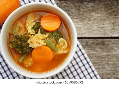 Kang Som Thai food. Spicy and sour soup with mix vegetables in white bowl. Soup from fish and herb mix of carrot, broccoli, long bean and chinese cabbage. Still life food. Popular food in Thailand.