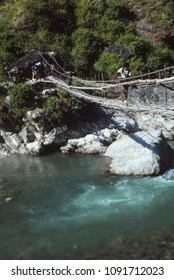 KANGCHENJUNGA HIMAL, NEPAL - NOV 14, 1987 - Hiker crossing suspension bridge over river,Kangchenjunga Himalayas, Asia