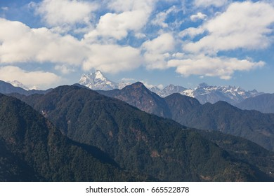 Kangchenjunga mountain with clouds above. Among green hills that view in the evening in North Sikkim, India.