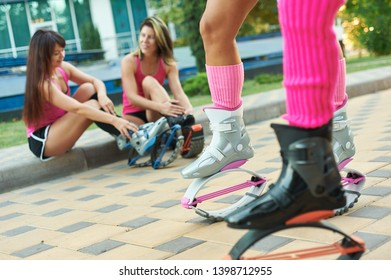 kangoo jumping fitness women team in boots. close up shot with blurred background. black and pink colours boots. fitness training concept