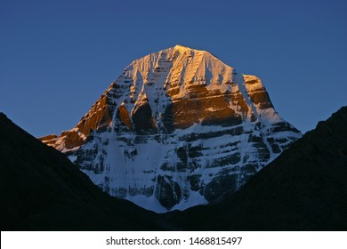 The Kangrinboqe Mountain (mount kailash) in Tibet is a sacred mountain of Buddhism and Hindu worship. It is considered to be the center of the world, and the golden sunset shines at the summit.