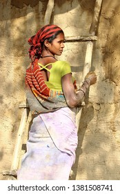Kanha, India – March 6, 2019: In a village near Kanha National Park, a young woman, over a ladder, is plastering her house