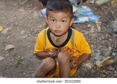 KANJANABURI,THAILAND-DEC 13: Children look at and eating chicken and sticky rice in hand from donation on Dec 13,2015 on high mounten backcountry Kanjanaburi,Thailand.