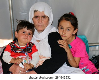 KANKE REFUGEE CAMP, DOHUK, KURDISTAN, IRAQ - 2015 JULY 4  - A Yazidi grandmother and her two child who escaped from ISIS inside her tent in Kanke refugee camp.