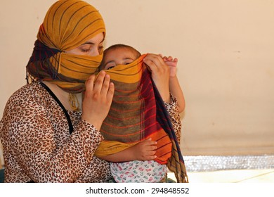 KANKE REFUGEE CAMP, DOHUK, KURDISTAN, IRAQ - 2015 JULY 4  - A Yazidi mother and her child who escaped abuse from ISIS inside her tent in Kanke refugee camp