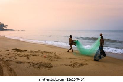 KANNUR, INDIA - DECEMBER 01, 2011: Local fishermen prepare to cast fishing net into Arabian Sea on a fine dawn morning along sandy beach on December 01, 2011 near Kannur, Kerala, India.