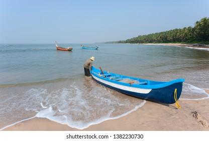 KANNUR, INDIA - DECEMBER 10, 2011: Unidentified fisherman next to fishing boat on Chera beach (Thottada) looking out to Arabian Sea on December 10 2011 near Kannur, Kerala, India.