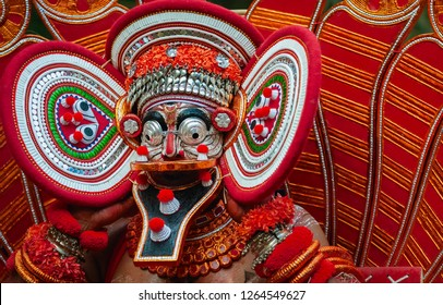 KANNUR, INDIA - DECEMBER 11, 2011: A Theyyam performer in colourful costume, face mask, during a performance of Theyyam in a small village on December 11, 2011 near Kannur, Kerala, India.