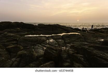 KANNUR, INDIA - DECEMBER 13, 2011: Locals shell fish on Chera rock at dusk with view of Arabian Sea near Thottada village, Kannur, Kerala, India.