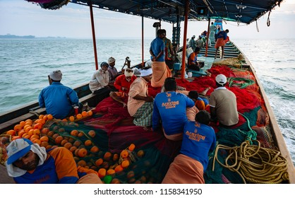 KANNUR, INDIA - DECEMBER 22, 2011: Crew take a rest on deep sea fishing trip in wooden boat in the Arabian Sea on a calm monsoon morning on December 22, 2011 near Kannur, Kerala, India.