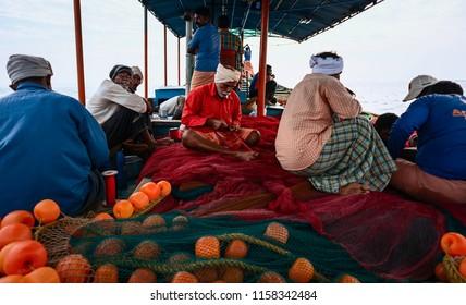 KANNUR, INDIA - DECEMBER 22, 2011: Crew repair net on deep sea fishing trip in wooden boat in the Arabian Sea on a calm monsoon morning on December 22, 2011 near Kannur, Kerala, India.