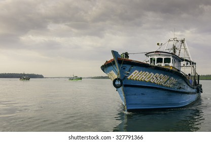 KANNUR, INDIA - DECEMBER 30, 2011: Trawlers return at dusk from deep sea fishing trip in Arabian Sea and anchor at Valapattam harbour on December 30, 2011 near Kannur, Kerala, India.
