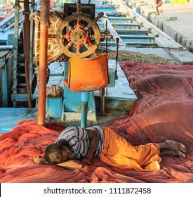 KANNUR, INDIA - January 10, 2017:  Kerala fisherman taking an evening nap inside the fishing boat at Kannur harbour, Kerala, India.