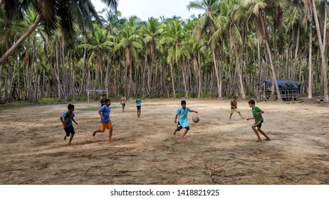 KANNUR, INDIA - JUNE 02: Group of children playing football in the center of a  Field on June 02, 2019 in Kannur, Kerala, India