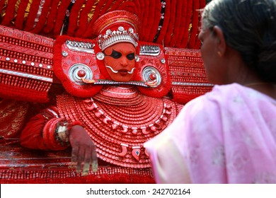 KANNUR - JAN 05: A Theyyam performer gives blessings to a devotee during the annual festival held at Kadannappalli Muchilot Bhagavati temple on January 05, 2015 in Kannur, India.