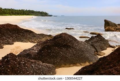 Kannur, Kerala, India. Beautiful tropical sandy beach with rock formations and palm trees flanked by Arabian Sea at dusk near Kannur, Kerala, India.