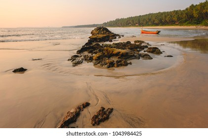 Kannur, Kerala, India. Chera rock in midst of sandy beach and wooden boat overlooking Arabian sea at sunset near Thottada village, Kannur, Kerala, India.