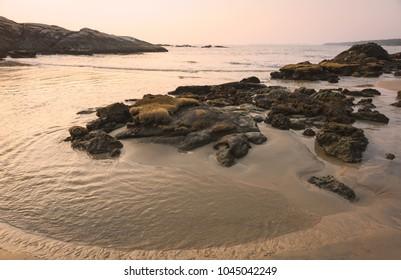 Kannur, Kerala, India. Chera rock in midst of sandy beach and wooden boat overlooking Arabian sea at sunset near Thottada village, Kannur, Kerala, India.