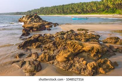 Kannur, Kerala, India. Chera rock in midst of sandy palm-lined beach and wooden boat overlooking Arabian sea at sunset near Thottada village, Kannur, Kerala, India.